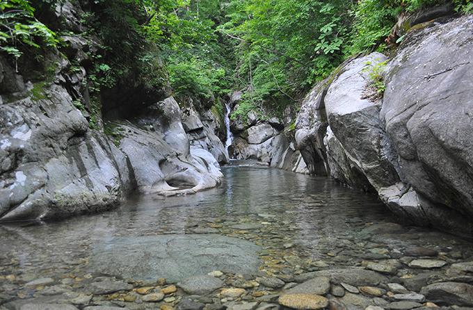 わき水のような透き通った水が流れる。上流は岩壁の迫る狭い流れとなっている。