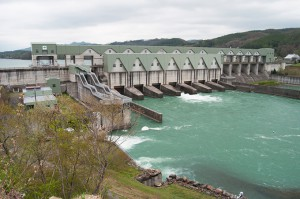 右岸から見た二風谷ダム:ダムの下部から放水する7門のオリフィスゲート(1門から放水中)。魚道の陰で見えないが、オーバフローさせるクレストゲート1門がある。その手前が東洋で唯一の豪華な可動式(ダムの水位によって上下できるエレベーター式)魚道。