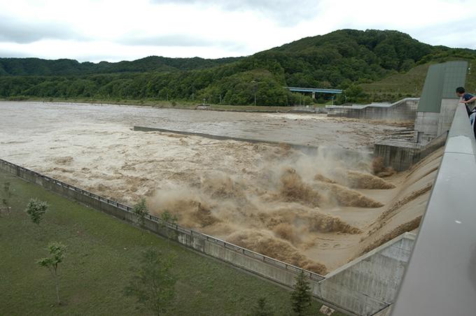 二風谷ダムは「ただし書き操作」の放流中。手前はクレストゲート5門からの放水。