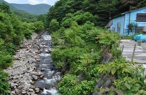 住宅の脇の橋から上流を見たら、やはり、川底に河川を横断する工作物が設置されている。2011年8月9日