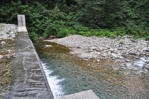 同、治山ダムの直下。治山ダムから流れ出す砂利の大きさはサッカーボール大か、小石や微細砂、シルト(泥)ばかりだ。治山ダムの下流では川底の石がどんどん押し流されて、川底が下がっていく。そのため、川岸が崩れ、川に面した山の斜面が崩壊し、大量の土砂と流木が流れ出す。