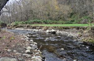 治山ダムの下流では、川底の砂利が流され、上流から砂利が補給されないために、川底が下がり、農地の縁が崩れている。