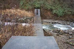 治山ダムを逆台形型にスリット化。ドリルで削岩している。