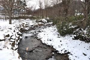 軍川の橋の上から川をのぞいてみた。上流側、右岸がコンクリートブロックで補修されていた。川岸が崩れたのである。2010年12月13日