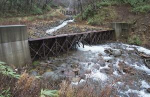 鉄格子型の治山ダムである。鉄格子の間口よりも大きな石や流木は止められる。石や流木が止められると、全ての砂利が止められることになり、全面コンクリートの治山ダムと同じになる。
