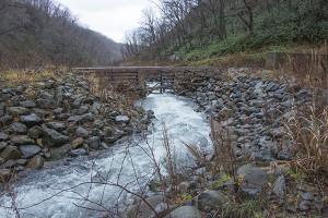 鉄格子型の治山ダムを上流から見る。鉄格子を塞いだ石や流木を取り除き、水が流れるように砂利を左右に振り分けている。メンテナンスが必要な治山ダムである。