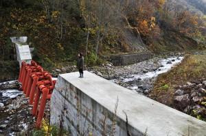治山ダム群の一番上の治山ダムである。中央部に鋼鉄製アングルが設置されている。巨石や流木はここで止められ、それが核になって砂利が止まるようになり、全面コンクリートダムと変わらぬ効果を発揮する。スリットのように見え、あたかも砂利が流れるかのように見えるが、コンクリートダムと全く変わらないのだ。砂利が流れるなどと誤解しないようにしてほしい。 治山ダムの下流、左岸の山裾が崩れている。工事の影響もあるのだろうが、今後、大規模に崩壊するとみている。2012年10月31日