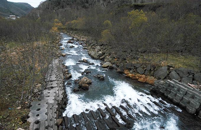 川底が下がらないように、川底にコンクリートブロックが敷き詰められている。その先は巨石が少ない。川底が下がり、右手のかわぎしが崩れているのが分かる。