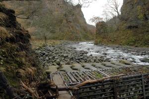 この治山ダムは砂利で満杯になっている。川幅が広がっており、その上を水が流れている。治山ダムで流速が小さくなるために、小ぶりの石が目立つ。渓流なのに、下流の景観をしている。