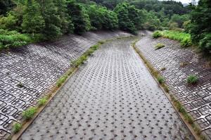 ダムからオーバーフローした水が流れる水路はびっしりとブロックが敷き詰められている。