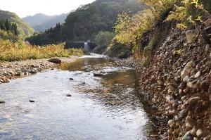 川岸は砂山崩しのように砂利が抜かれ、垂直の崖になっている。上流にダムが見える。
