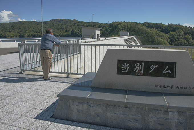 「流域の自然を考えるネットワーク」の宮崎司代表。すぐ脇には高橋はるみ北海道知事名の石が置かれていた。
