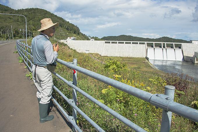長野県の「渓流保護ネットワーク」の田口康夫氏も現地視察した。後ろは完成した当別ダム