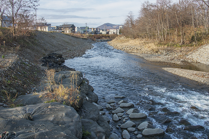 流路工で砂利が止められるため、下流では河床の砂利が流される。当然、左側の盛土は簡単に流される。2015年11月19日