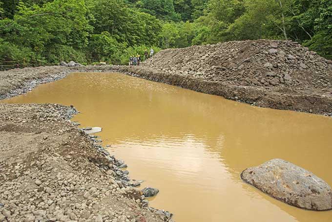 河床に溜まっていた泥を洗浄して集めた池なので、大量の泥だ。周りを土嚢で囲っても無い。増水すれば、ひとたまりもなく流れ出す。撮影:2016年8月29日