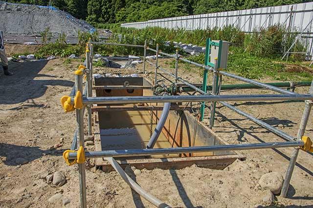 有害重金属含有掘削土から雨水で溶出した水は沈殿槽に集められ、ホースで吸い上げて、PAC処理施設へ送られるようになっていた。撮影:2016年7月12日