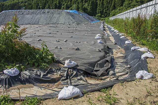 排水溝にはゴム製の遮水シートが敷かれたが、有害重金属含有の掘削土は防水シートの上にどんどん積み上げられている 撮影:2016年7月12日
