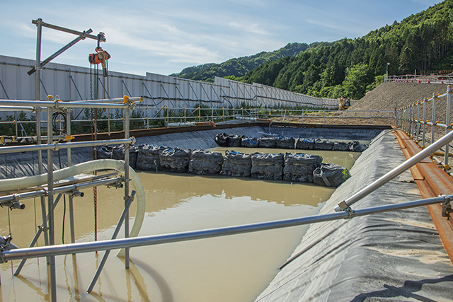 PAC処理施設で濁水処理しきれなかった濁水を再処理するために仮置きする濁水沈澱池を設置した。撮影:2016年7月12日
