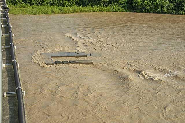 貯砂ダム(堰)を越えて流れ込むひどい泥水
