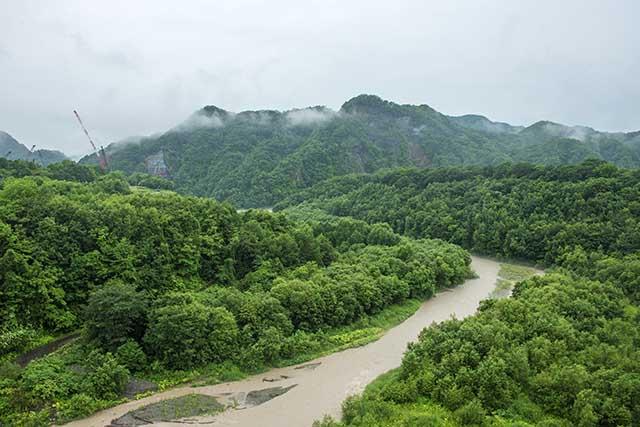 額平川の支流宿主別川の橋の上から平取ダム建設現場を見る。正面の山が神聖な山「チノミシリ」である。